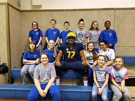Bryce Harris posed last year with some students from St. Pius X Catholic School in Toledo.